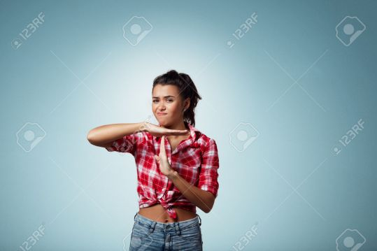 Closeup portrait of attractive young serious woman showing time out gesture with hands, isolated on blue background. Negative human emotion facial expression sign symbols,body language attitude